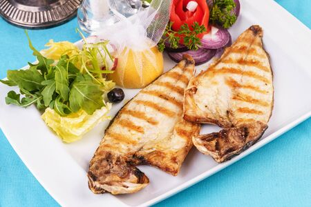European cuisine, Mediterranean dish. steak of river fish with white meat, served with vegetables, lemon and arugula and tomato salad Stockfoto - 130801208
