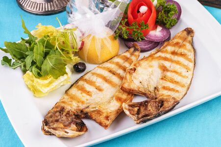 European cuisine, Mediterranean dish. steak of river fish with white meat, served with vegetables, lemon and arugula and tomato salad Stockfoto - 130801209