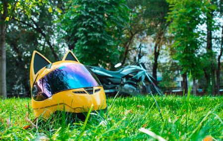 The yellow helmet of a biker girl from a motorcycle with mirror glass and ears lies on the green grass against the background of a gray motorcycle in autumn.