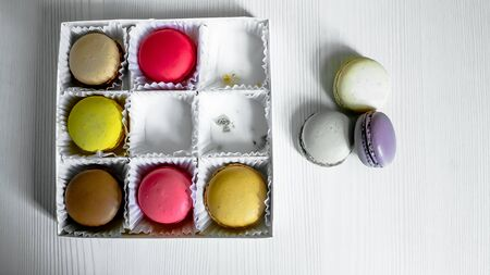 White pack with Macarons cookie, on a white wooden background. View from above.