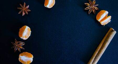 Dark textured christmas background with tangerine slices, citrus leaves, star anise and cinnamon sticks. Background for banner, view from above.