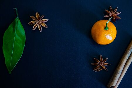 Dark textured christmas background with mandarin, citrus leaves, star anise and cinnamon sticks. Background for banner, copyspace. view from above.