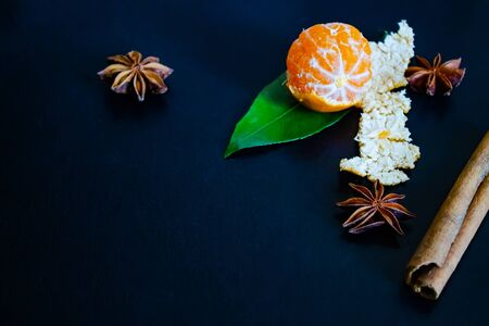 view from above.Dark textured christmas background with peeled tangerines, citrus leaves, star anise and cinnamon sticks. Background for banner, copyspace.