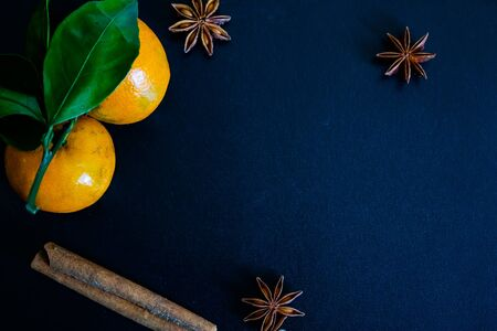 Dark textured christmas background with two tangerines, citrus leaves, star anise and cinnamon sticks. Background for banner. view from above. Stockfoto