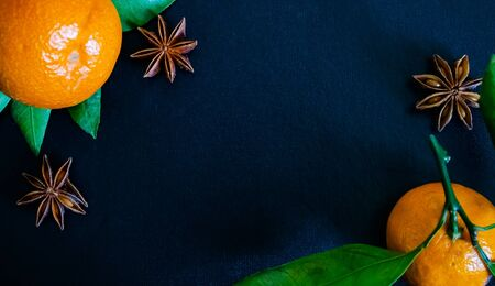 Dark textured christmas background with two tangerines, citrus leaves, star anise and cinnamon sticks. Background for banner, view from above.