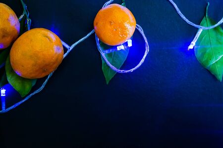 Dark textured Christmas background with tangerines, citrus leaves and a glowing Christmas blue garland. Background for banner, view from above. Stockfoto