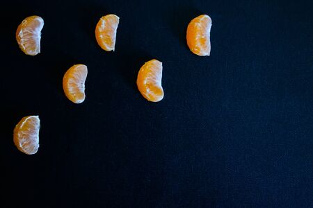 Dark textured christmas background with tangerine slices. Background for banner, copyspace. view from above.