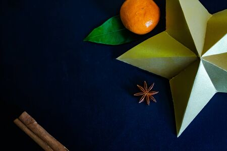 Dark textured christmas background with tangerines, citrus leaves, star anise, artificial star and cinnamon sticks. Background for banner, copyspace. view from above. Stockfoto