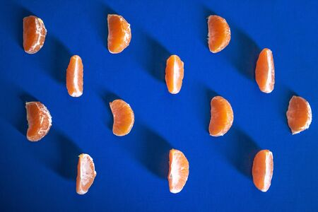 Light blue textured Christmas background with tangerine slices. Background for banner, copyspace. view from above.