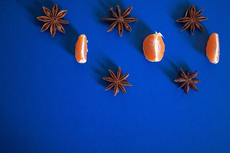 Light blue textured Christmas background with slices of tangerines, star anise. Background for banner, view from above.