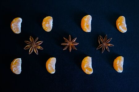 Dark textured Christmas background with slices of tangerines, star anise. Background for banner, view from above.