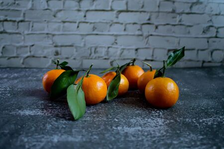 Gray concrete background with a brick wall, tangerines with leaves and twigs view from the top. New Year, in the style of health.