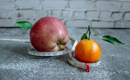 Red apple and orange for weight loss while dieting, centimeter measuring tape Stockfoto