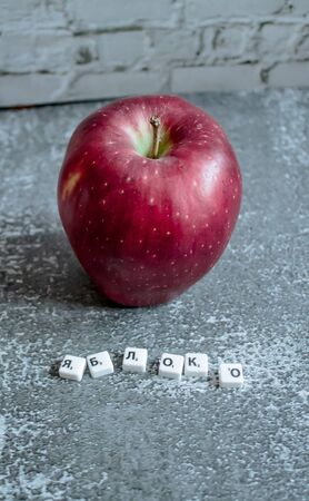 Gray background, red apple top view. The inscription apple in Russian.