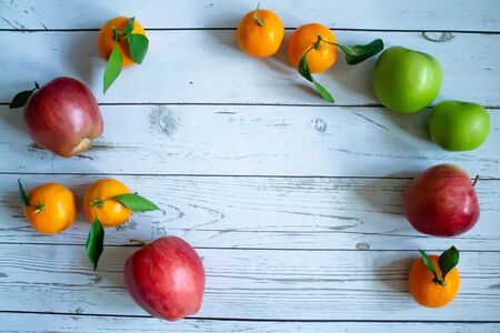 Light gray wooden background, oranges with leaves and twigs, view of red and green apples from the top. the style of health and proper nutrition.