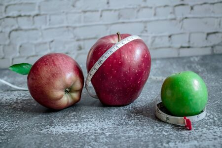 red and green apple for weight loss while dieting, centimeter measuring tape