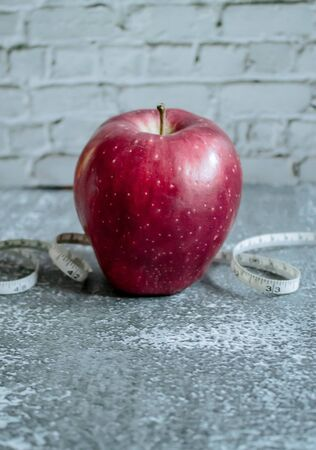 red apple for weight loss while dieting, centimeter measuring tape, on gray background Stockfoto