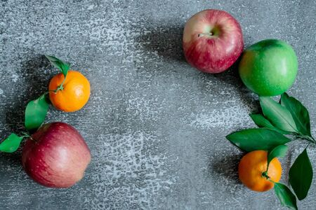 Gray concrete background, tangerines with leaves and twigs, red and green apples view from the top. Place for an inscription, New Year Stockfoto