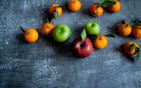Gray concrete background with a brick wall, tangerines with leaves and twigs, red and green apples view from the top. New Year, in the style of health.