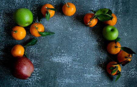 Gray concrete background, tangerines with leaves and twigs, red and green apples view from the top. Place for an inscription, New Year, in the style of health.