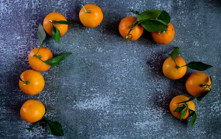 Gray concrete background, tangerines with leaves and twigs, view from the top. Place for an inscription, New Year banner. Stockfoto