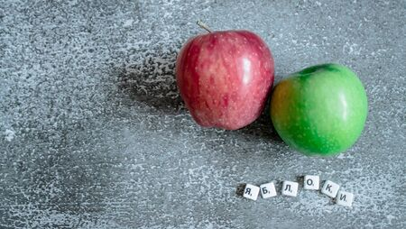 Gray background,, red and green apples view from the top. The inscription apples in Russian.