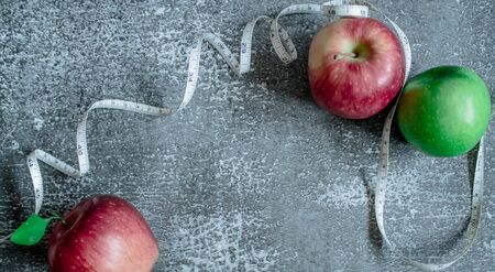 red and green apple for weight loss while dieting, centimeter measuring tape, on a gray background, top view, copy space Stockfoto