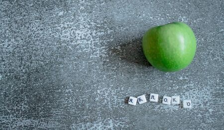 Gray background, green apple top view. The inscription apple in Russian. Background in the style of health.