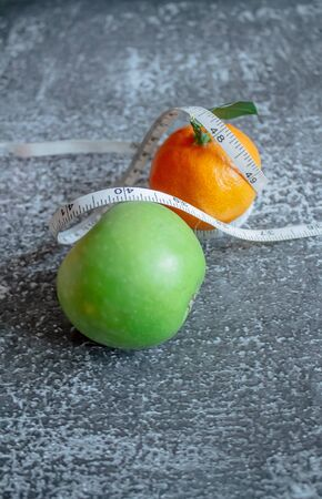 green apple and orange for weight loss while dieting, centimeter measuring tape