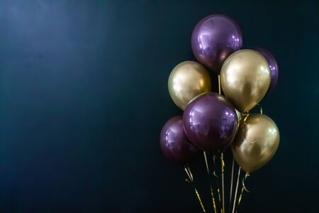 Set of gold and purple balls on a dark background. Holiday concept, postcard, copyspace.