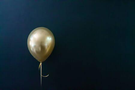 golden balloon on a dark background. Holiday Concept, Postcard, Copyspace.