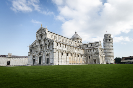 Color photograph of the architectural group formed by the Cathedral and the Tower of Pisa (Italy), in the foreground you can see a large space of grass, all trimmed against a background of blue sky and white clouds.