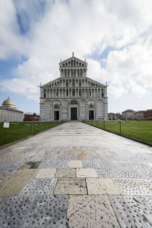 Color photograph of a tiled path leading to the Cathedral of Pisa (Italy), which is outlined against a background of blue sky with white clouds. Stock Photo