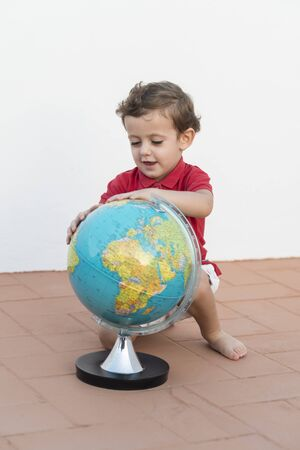 Color photography of a child playing with a globe. Stock Photo