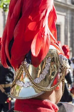 Detail of a red feathered helmet of a musician.