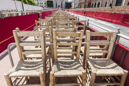 Empty chairs placed in a section of the route that will make the brotherhoods in their penitential journey, ready to be occupied by the public. Stock Photo