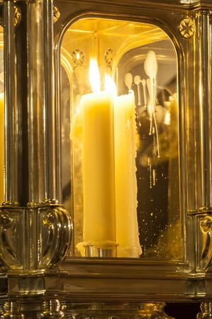 Detail of a lit candle inside a lantern.