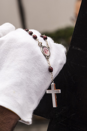 Detail of the hand of a penitent with a rosary, counting the beads while praying.