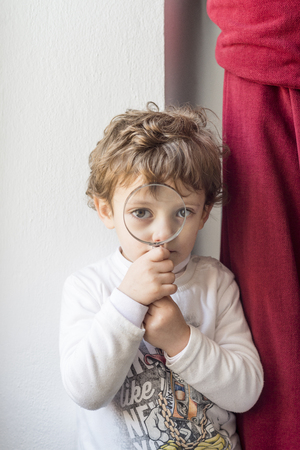 Child next to a red curtain looking with a magnifying glass