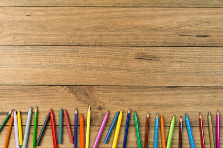 Concept of back to school. Marker pens and colored pencils on wooden boards.