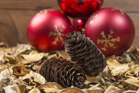 Pine cone on dried leaves and red christmas balls in the background