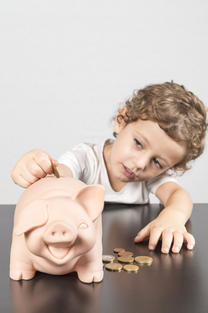 Child inserting coins in a piggy bank Reklamní fotografie