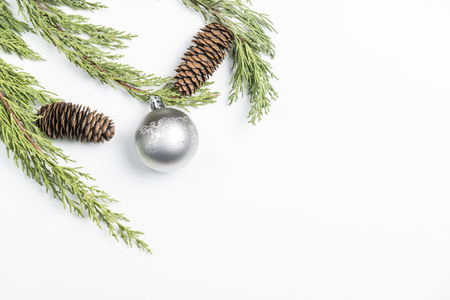 Christmas background made with pine branches, pine cones and Christmas decorations on white background.
