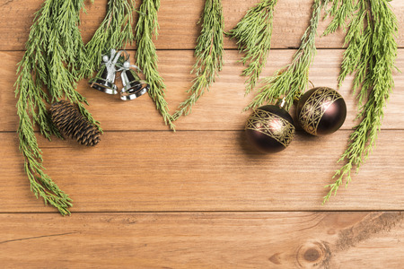 Christmas background made with pine branches, pine cones and Christmas decorations on wooden background.