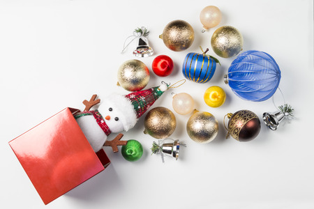 Red box of Christmas decorations on white background.