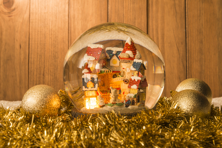 Christmas crystal ball and christmas decorations on garlands with a background of wooden boards.