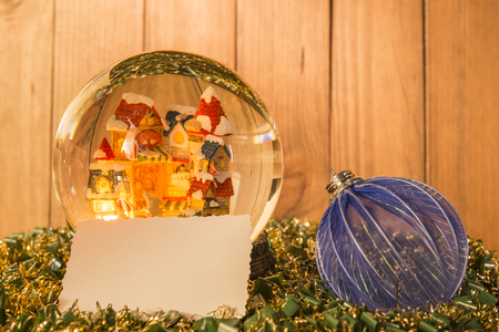 Christmas crystal ball, greeting card and christmas decorations on garlands with a background of wooden boards.