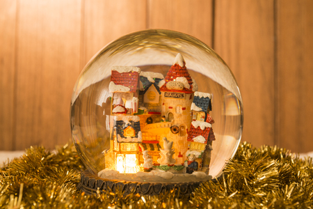 Christmas crystal ball on garlands with a background of wooden boards.