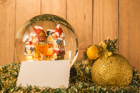 Christmas crystal ball, greeting card and christmas decorations on garlands with a background of wooden boards. Banco de Imagens