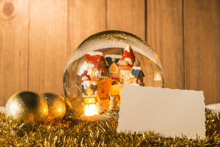 Christmas crystal ball, greeting card and christmas decorations on garlands with a background of wooden boards. Imagens